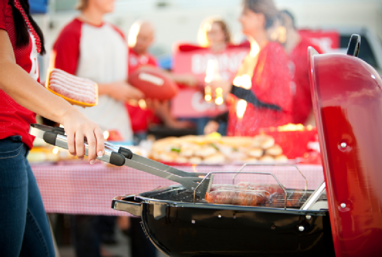 Tailgating: Woman Grilling Bratwurst for Party